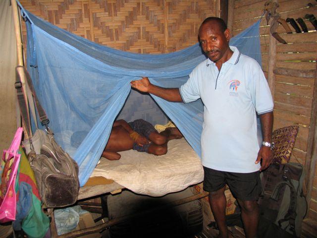 adi-malaria-officer-giwi-yombo-demonstrating-use-of-llin-net
